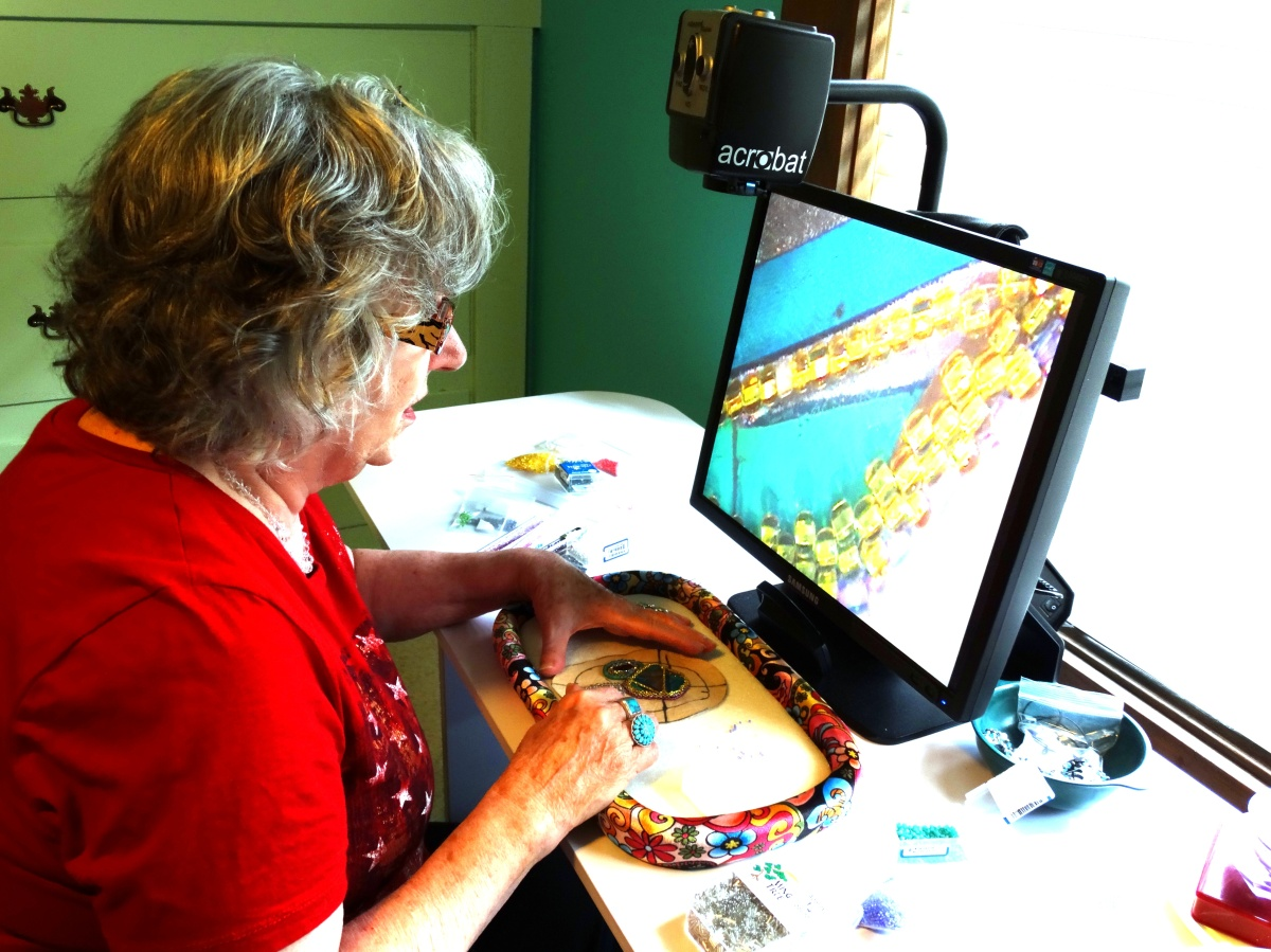 Photo shows the author, Lynda McKinney Lambert, at work using an aCROBAT CCTV to help her make her art. Lynda is blind. She creates award-winning fiber and bead work arts, and writes books.