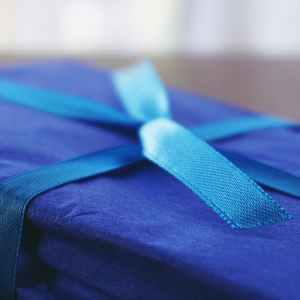 Photo of a gift wrapped in blue paper with a blue satin ribbon.