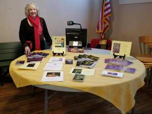 Lynda Lambert stands beside her book display on the table at a book siging event. She is wearing a red wool jacket made in Austria. She is smiling and her books are arrayed on a round table covered with a yellow cloth.